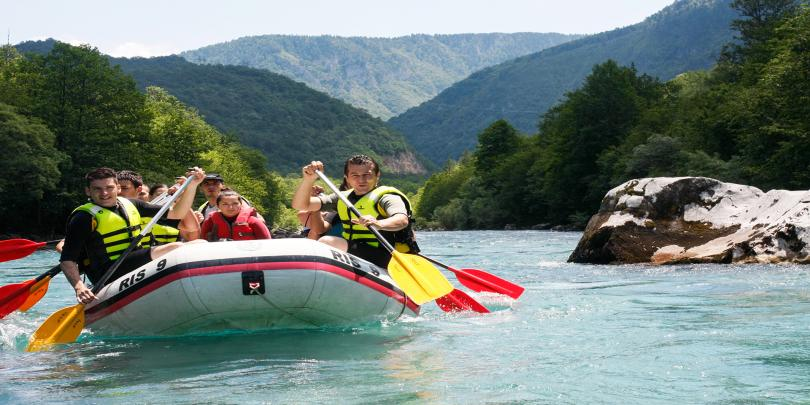 Group of students whitewater rafting on a river.