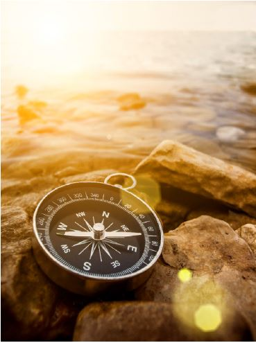 Compass on some rocks close to beach