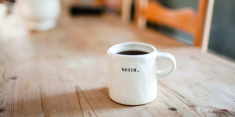 "coffee cup with the word ""begin"" on it."