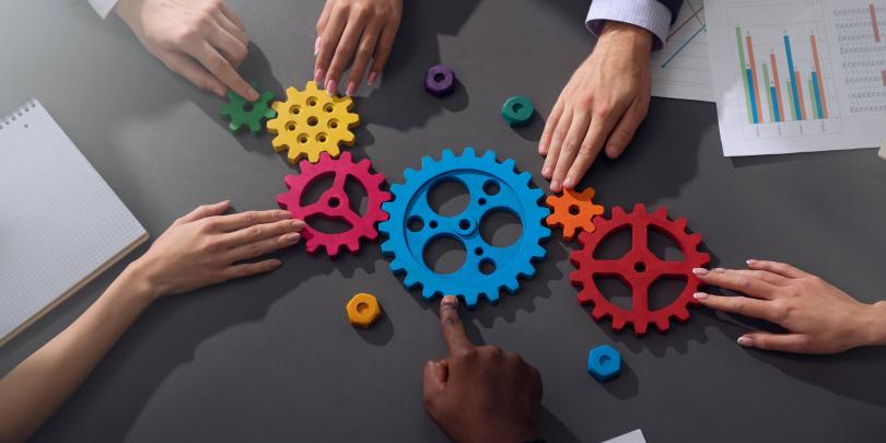 People's hands on gears to illustrate teamwork