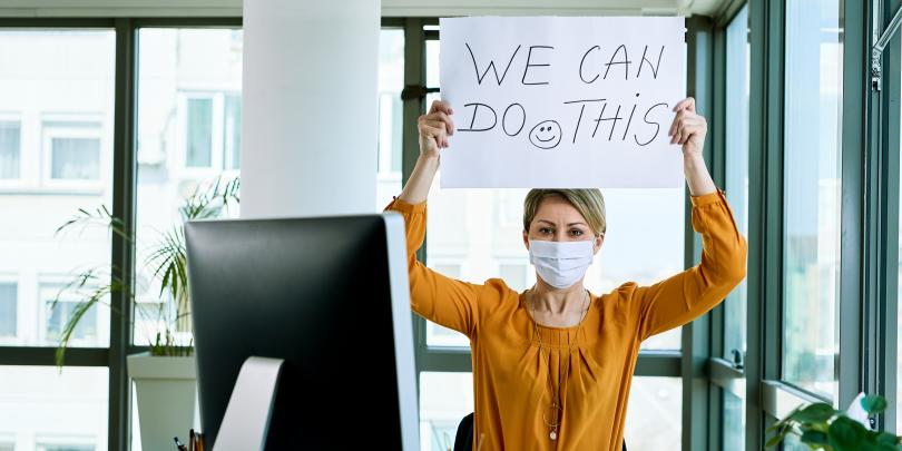 "Woman in mask holding up ""We Can Do This"" sign"