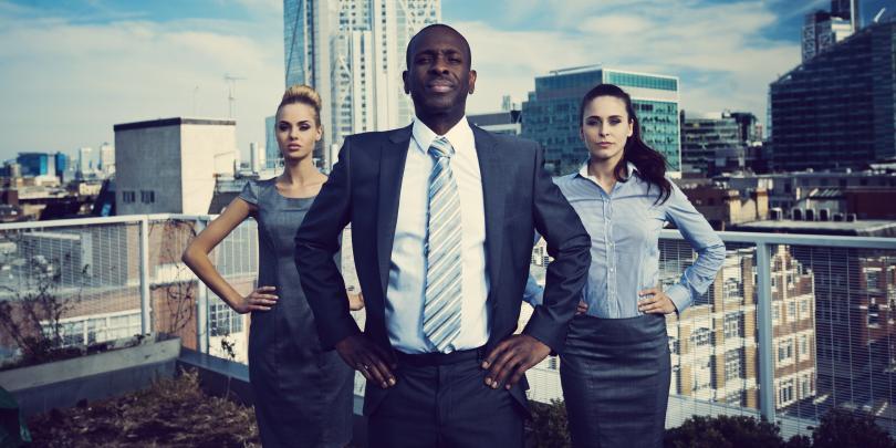 Three businesspeople posing like superheroes on a roof