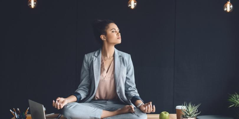 Female leader meditating in office