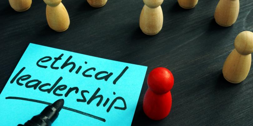 "The words ""ethical leadership"" next to small wooden figures"