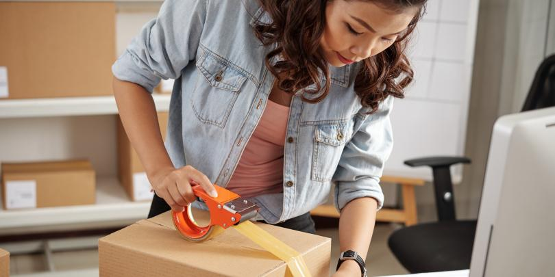 Woman taping up a package for delivery