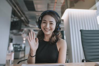 Woman waving hi to camera