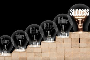 burned out light bulbs saying failure leading up to one saying success