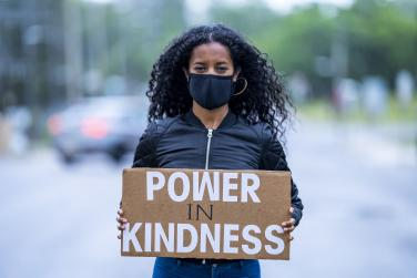 Woman in mask holding sign that says Power in Kindness