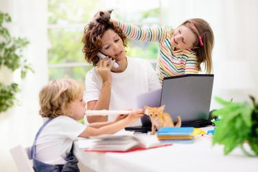 Mom working from home with kids all over her