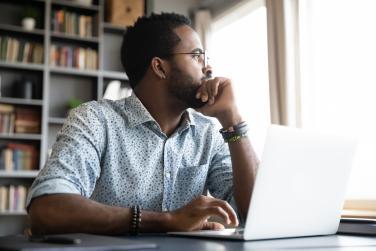 Man at laptop looking thoughtful