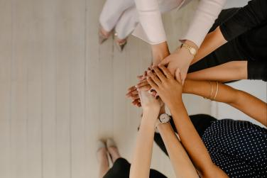 Women putting their hands together in solidarity