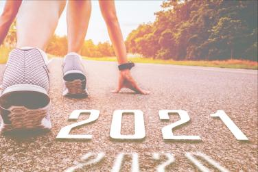 """Person getting ready to race with """"2021"""" written on the pavement"""