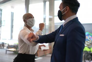 People in COVID masks bumping elbows in an office environment