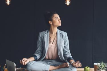 Female leader meditating in office