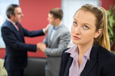 Woman looking unhappy as two co-workers in the background shake hands