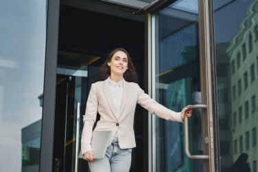 Woman walking happily out of the office