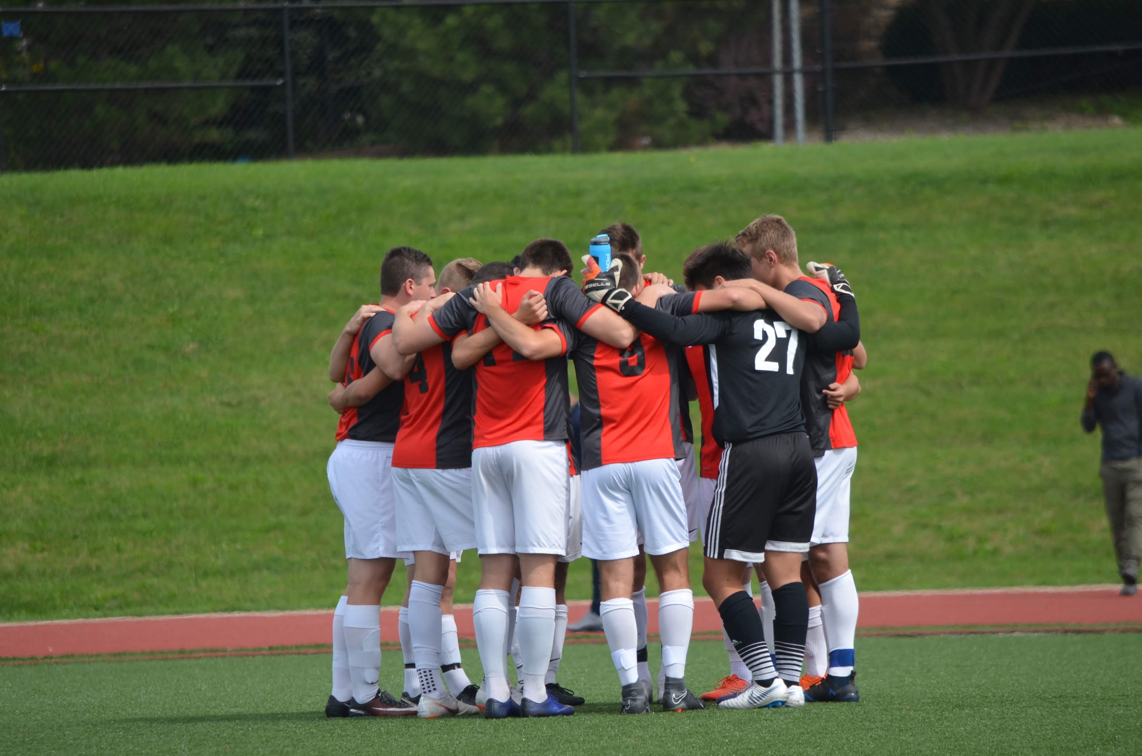 David McGrath in men's soccer club team huddle