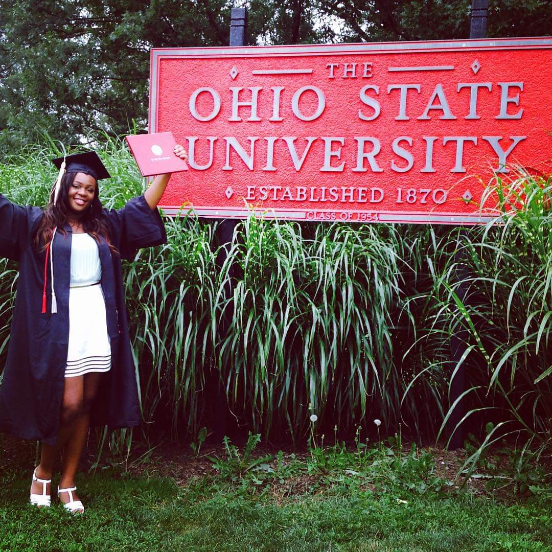 Amber Hammond in graduation cap and gown by Ohio State sign
