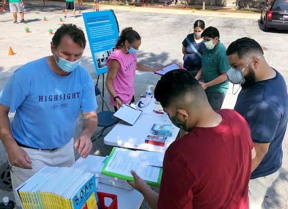 Mark Duhon and staff member Patty Hart distribute materials to rising freshmen.