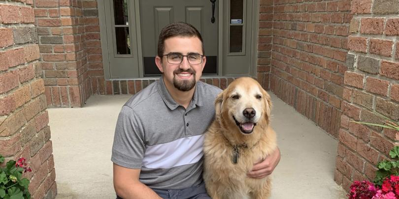 Nick Lenyo and dog on front porch of home