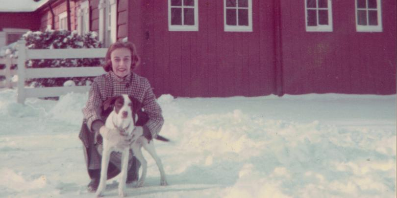 Marilyn Rogers Becker and her dog, Molly outside in snow by red house